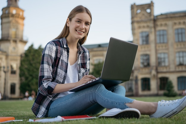 Улыбающийся студент учится онлайн с помощью портативного компьютера, сидя в университетском городке
