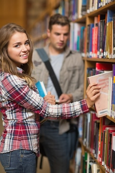 Smiling student taking book from shelf in library at the university