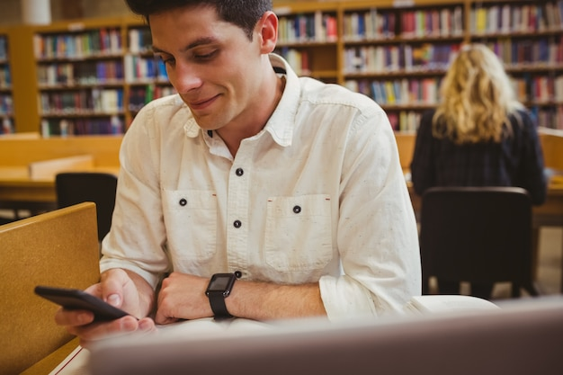 Smiling student using his smartphone in library