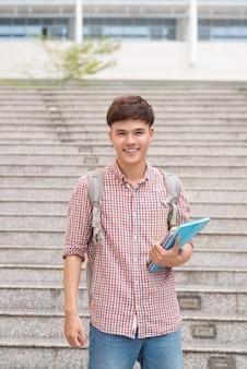 Улыбающийся студент с его книгами в университете