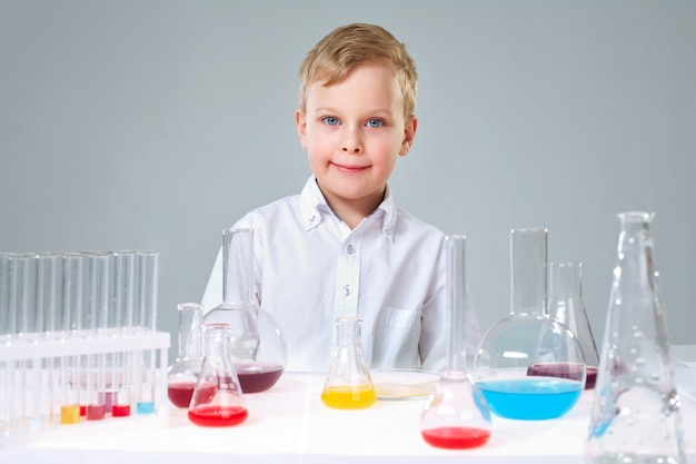 Smiling student with test tubes and flasks