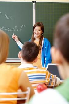 Улыбаясь студент писать математику на доске