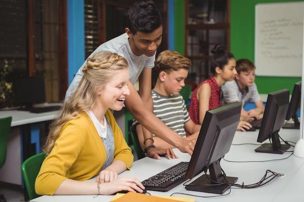 컴퓨터 교실에서 공부하는 웃는 학생