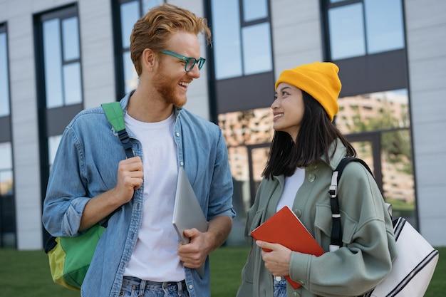 大学のキャンパスで話したり歩いたりする笑顔の学生
