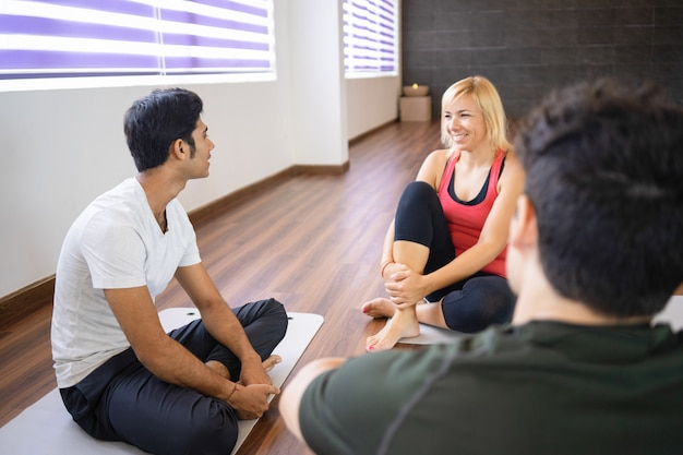 Smiling students talking with instructor after yoga class