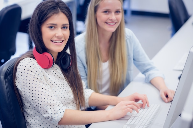 Smiling students using computer at university