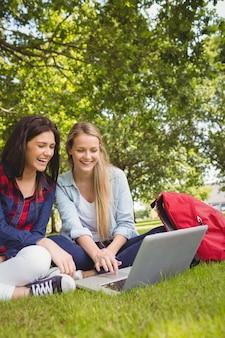 공원에서 노트북을 사용 하여 웃는 학생