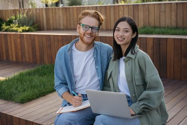 カメラを見て一緒に勉強しているラップトップコンピュータを使用して笑顔の学生