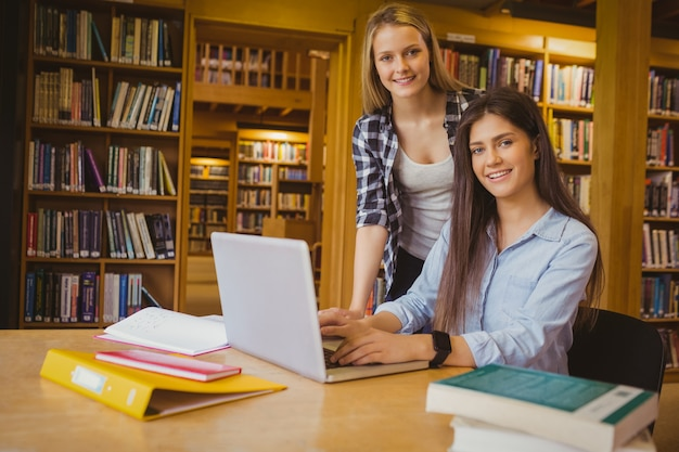 Smiling students using laptop in library