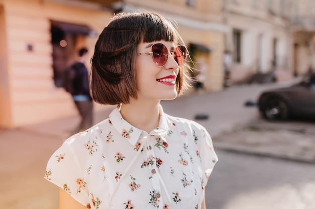 Улыбаясь потрясающая женщина в модной блузке позирует на городе. довольно кавказская девушка с черными волосами охлаждает солнечным утром.