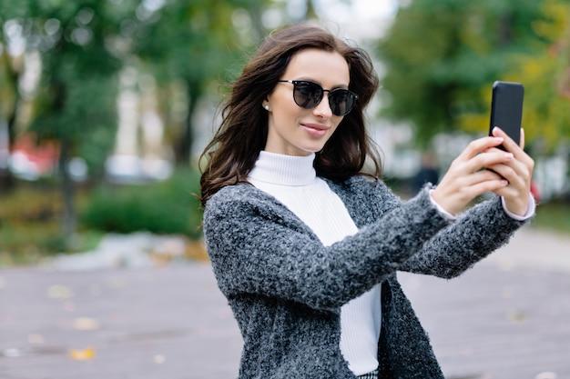 공원에서 산책을 즐기고 셀카를 만드는 검은 머리와 웃는 스타일 소녀. 아름다운 가을 공원 옆에 자신의 사진을 찍는 패션 복장에 젊은 웃는 여자의 야외 초상화