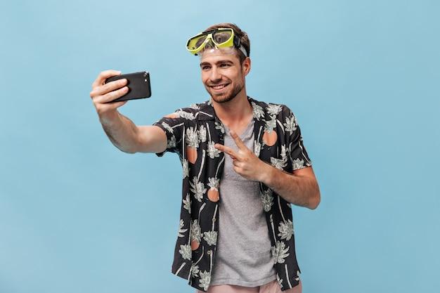 Sorridente elegante uomo barbuto in camicia nera estiva e occhiali da nuoto verdi freschi fa foto, mostrando segno di pace e sorridendo