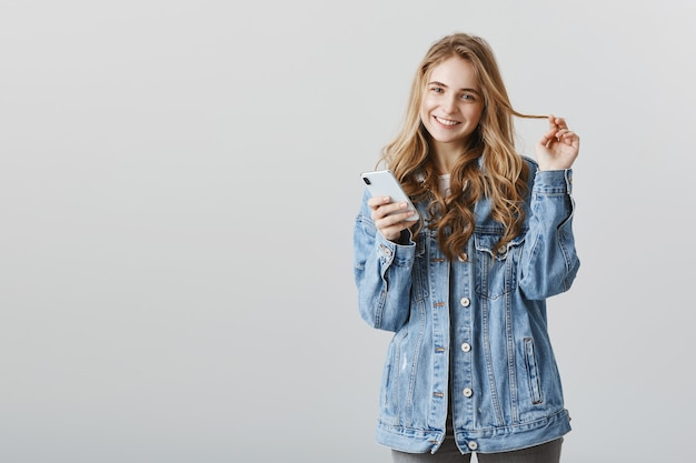 Smiling stylish blond girl shopping online, using smartphone app