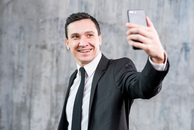 Smiling stylish businessman taking selfie with smartphone