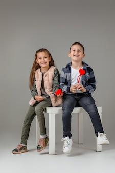 Улыбаясь стильная маленькая пара, ребенок девочка и мальчик с красными сердцами на палочке в модной одежде, сидя вместе