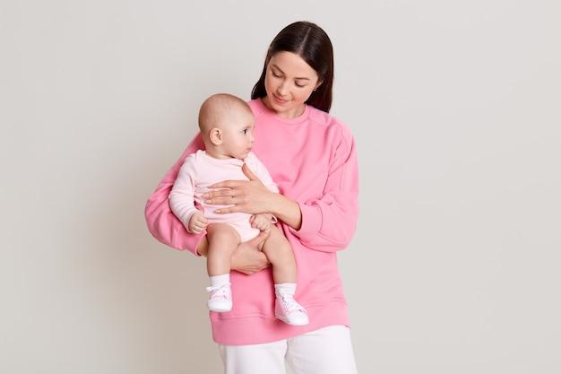 Улыбающаяся стильная мать держит девочку до 1 года, мама в повседневном розовом свитере, смотрит на своего ребенка, ребенок одевает боди, глядя в сторону.