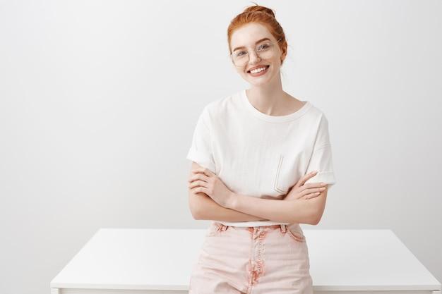 テーブルに寄りかかってスタイリッシュな赤毛の女の子の笑顔、決心して