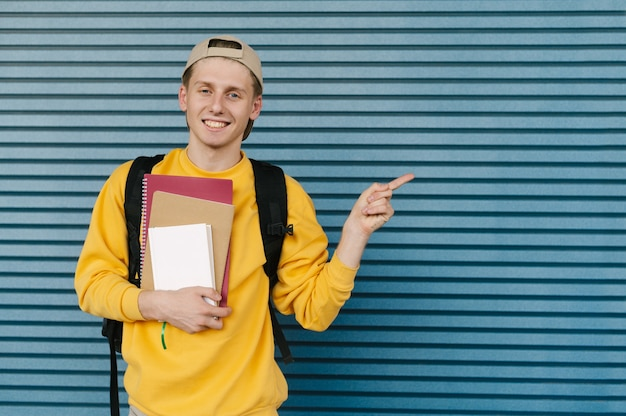 本とノートを手に持つスタイリッシュな学生の笑顔