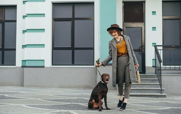 Улыбающаяся стильная женщина и коричневая собака на поводке