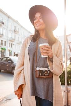 コーヒーカップを保持している笑顔のスタイリッシュな女性