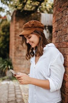 흰색 상단과 갈색 머리 장식에 웃는 세련 된 여자는 벽돌 벽에 기대어 전화 채팅입니다.