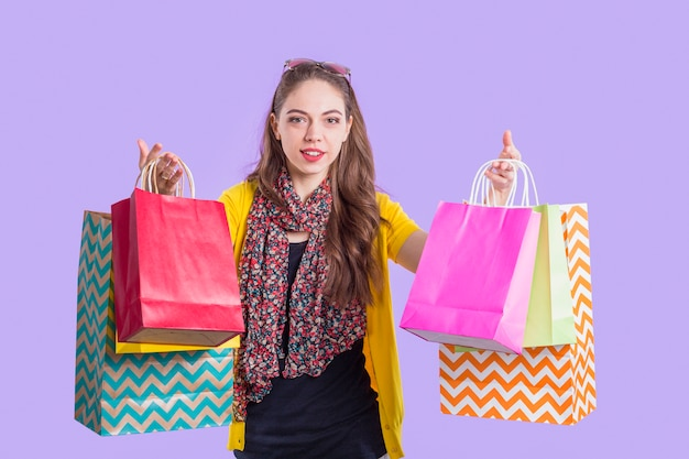 Smiling stylish woman showing colorful paper bag