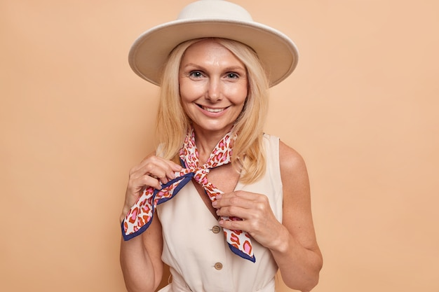Smiling stylish woman ties kerchief around neck wears fedora and summer dress has happy expession poses against brown wall