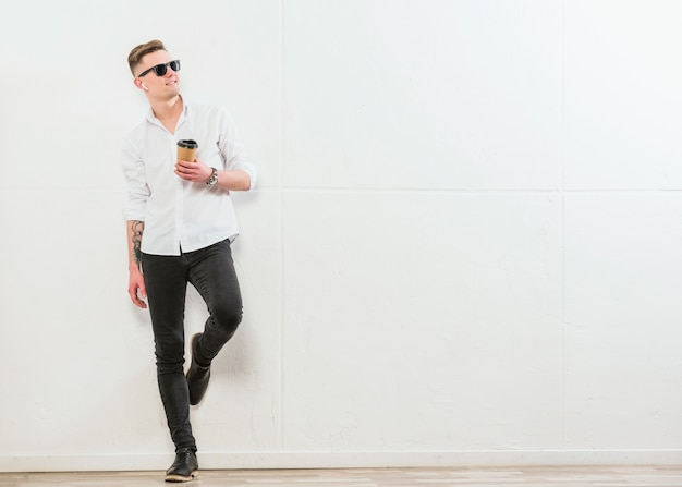 Smiling stylish young man holding takeaway disposable coffee cup standing against white wall