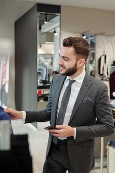 Улыбающийся стильный молодой человек в куртке стоит у стойки и держит смартфон, покупая одежду в магазине