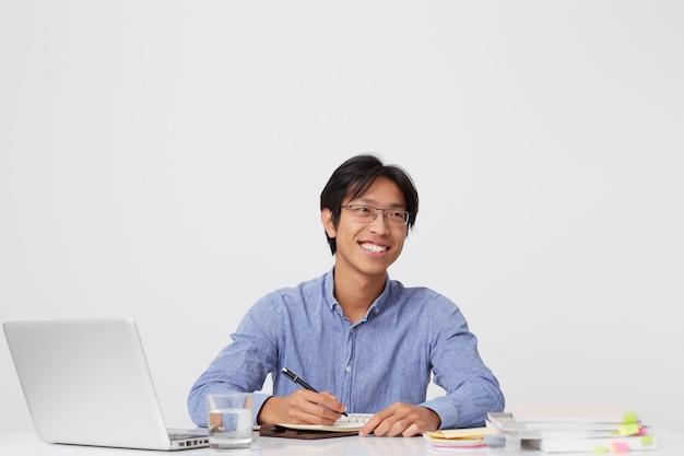 ノートパソコンでテーブルに座って、白い壁の向こう側を見てノートに書くことを計画している眼鏡で成功したアジアの若いビジネスマンを笑顔