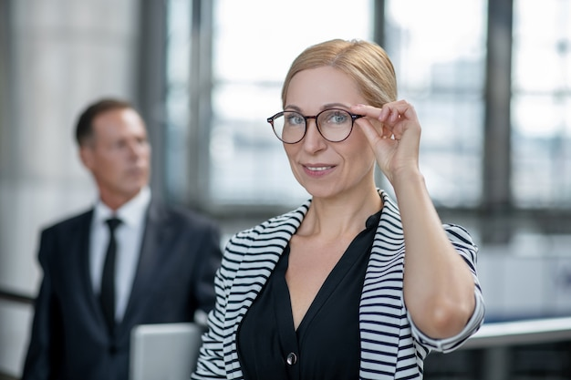 안경을 만지고 웃는 성공적인 비즈니스 여성