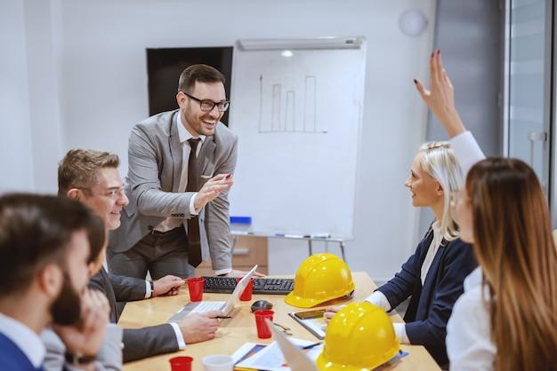 彼のチームが会議室に座って質問をしている間に立って新しいプロジェクトについて話している成功した実業家の笑顔。野望は空にはしごを置いています。