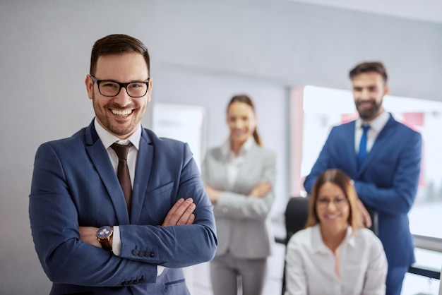 Smiling successful caucasian businessman in formal wear and with crossed arms standing in office. in background his team posing. successful entrepreneurs are givers and not takers of positive energy.