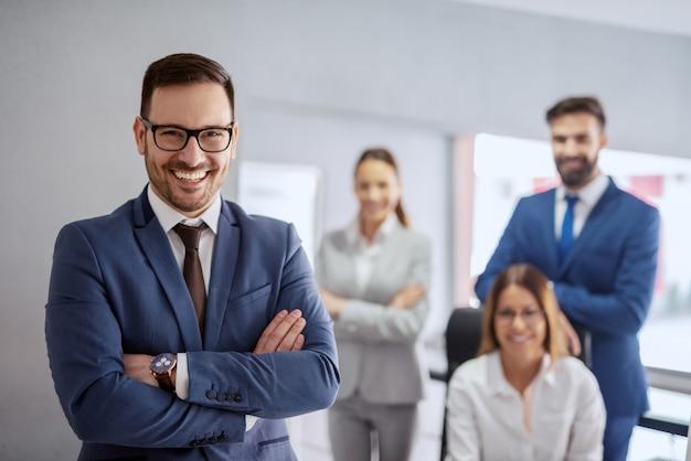 성공적인 백인 사업가 공식적인 마모 및 무기 사무실에서 서 웃 고. 백그라운드에서 그의 팀 포즈입니다. 성공적인 기업가는 긍정적 인 에너지를주는 사람이 아니라주는 사람입니다.