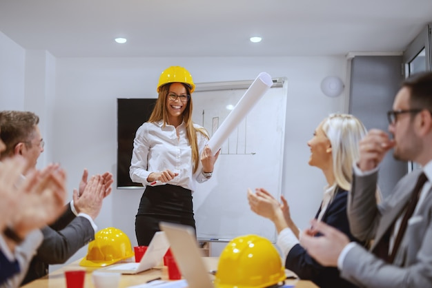 Smiling successful female architect standing at boardroom and talking about new project. coworkers clapping to her. if you do what you always did, you will get what you always got.