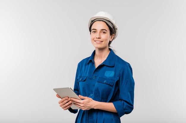 격리 된 네트워킹 동안 터치 패드를 사용하여 작업복 및 안전모에서 성공적인 여성 엔지니어 미소 짓기