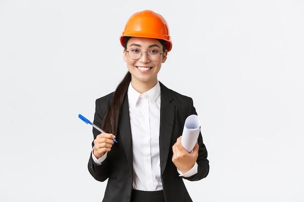 Blueprを保持しているヘルメットとスーツで成功した女性起業家チーフ建設エンジニアの笑顔...