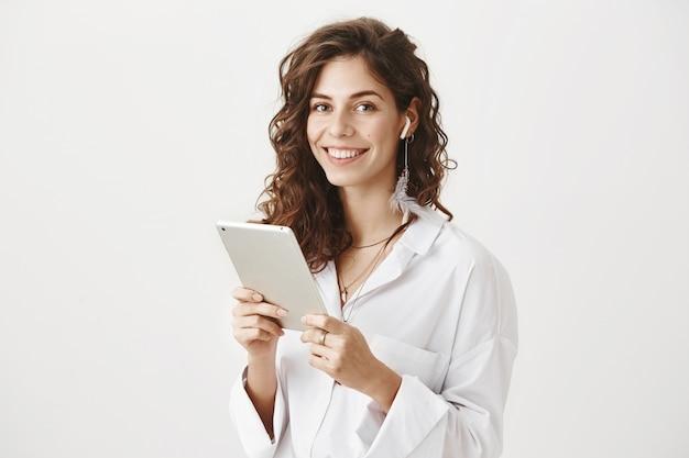 디지털 태블릿 무선 이어폰에 성공적인 여성 기업가 미소