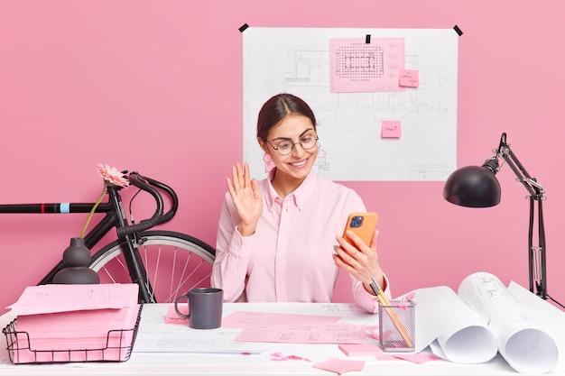 스마트 폰 카메라에 성공적인 여성 회사원 파도 손바닥을 웃고 코 워킹 공간에서 거리 전화 포즈를 취하고 청사진을 준비하여 프로젝트를 만들기위한 전략을 논의합니다. 무료 사진