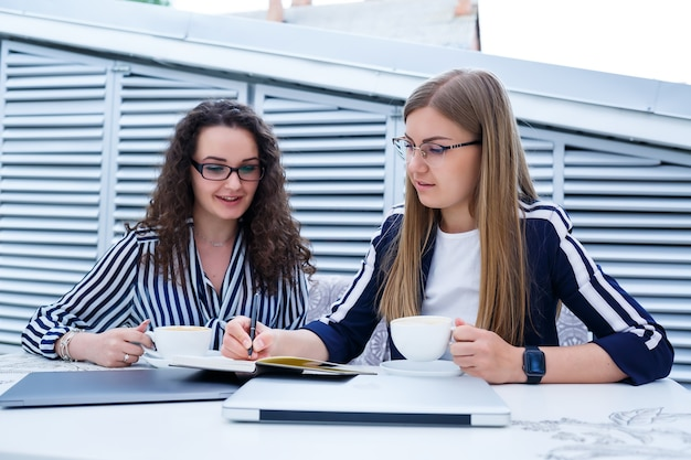 Улыбающиеся успешные работницы работают вместе, работают за ноутбуком на террасе, коллеги заняты обсуждением идей, девушки в кафе на деловой встрече. бизнес-концепция