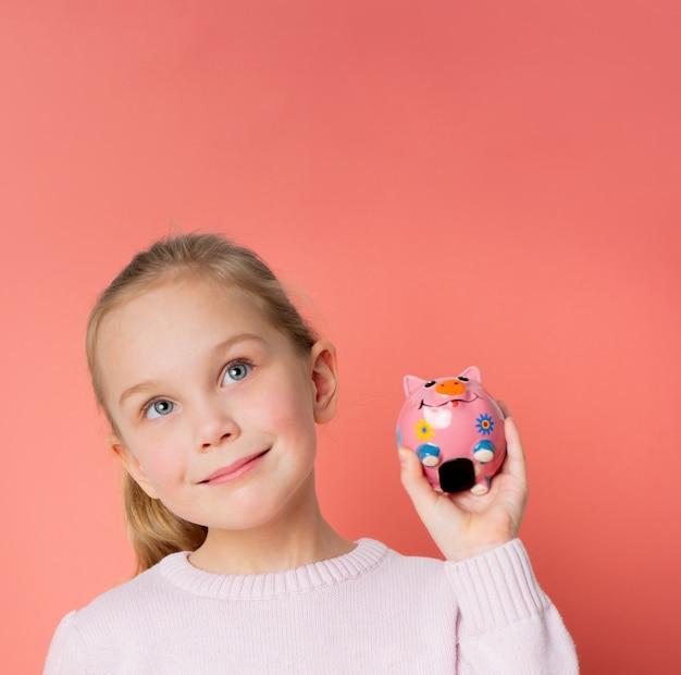 手のひらに貯金箱を保持しているセーターで5番目の成功した女の子の笑顔