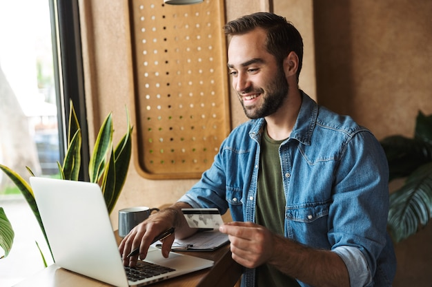 Smiling successful man wearing denim shirt holding credit card and typing on laptop while working in cafe indoors