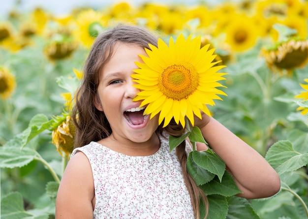 Smiling summer little caucasian girl holding sunflower near her eye. sunflowers field.