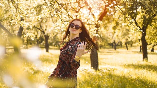 サングラスで笑顔の夏の女性。美しい若い女性の屋外。自然を楽しみます。春の公園で健康的な笑顔の女の子。晴れた日