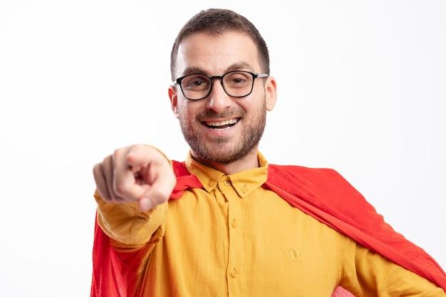 Улыбающийся человек супергероя в оптических очках с красными плащами спереди изолирован на белой стене