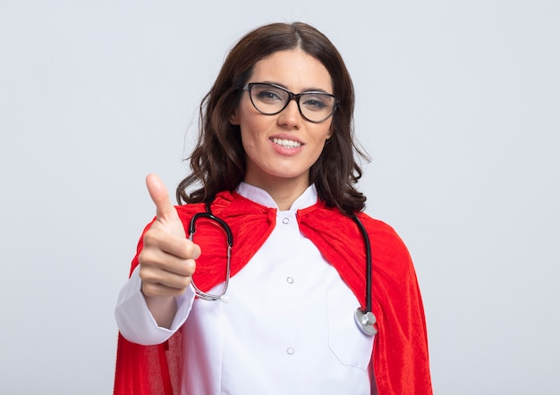 Sorridente superdonna in uniforme medico con mantello rosso e stetoscopio in vetri ottici pollice in alto isolato sul muro bianco