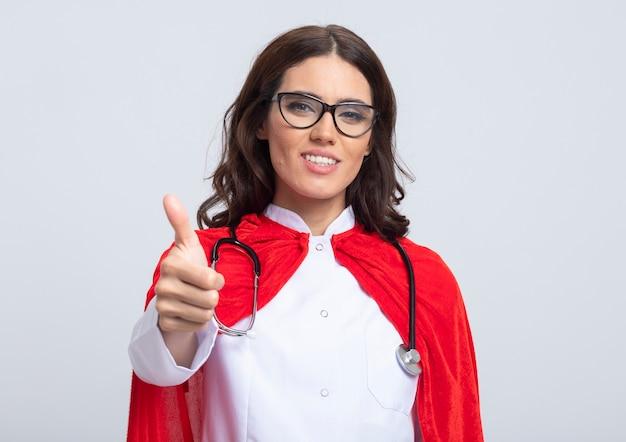Улыбающаяся суперженщина в униформе доктора с красной накидкой и стетоскопом в оптических очках показывает палец вверх, изолированную на белой стене