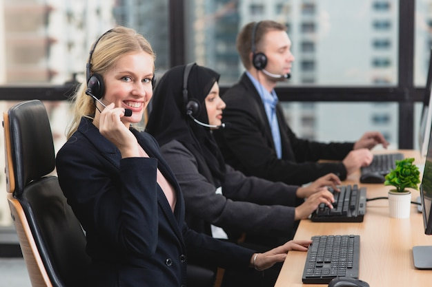 Smiling support operator with colleagues in headsets working in office