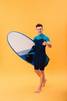 Улыбающийся серфер, идущий с доской для серфинга и указывающий