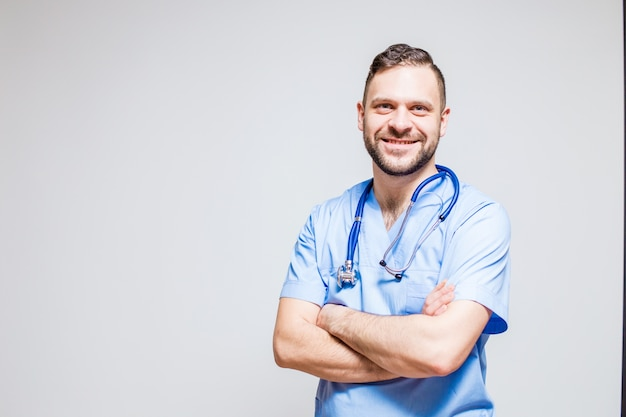 Smiling surgeon with a stethoscope at the neck and arms crossed